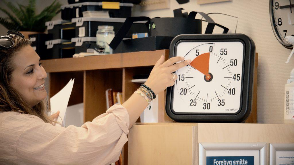 En pædagog indstiller time-timeren, hvilket er et redskab specialskolen i høj grad benytter sig af i undervisningen.